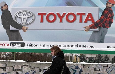 Una mujer pasea por una calle de Praga bajo un cartel de Toyota. |  Reuters