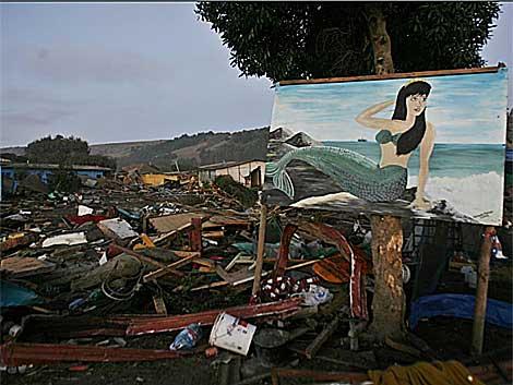 Un mural junto a casas destruidas en la localidad turística de Iloca, en la costa chilena. | Efe