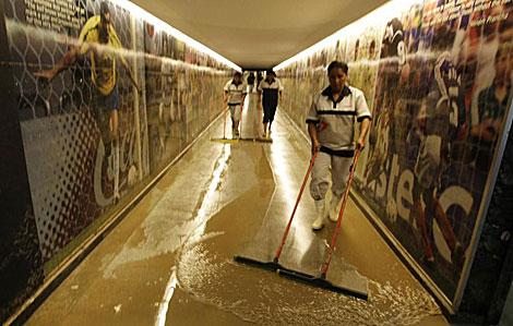 Una empleada limpia un túnel de acceso inundado en Maracaná. | Reuters