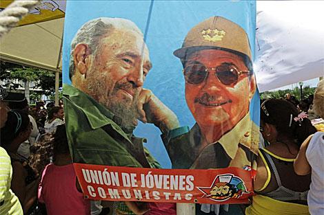 Jóvenes con una pancarta de los hermanos Castro. | Reuters