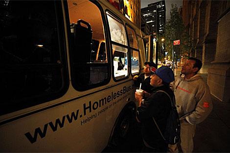 Grupo de personas sin techo recogiendo comida. | Reuters