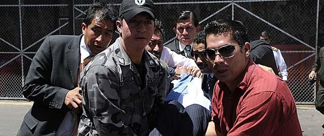 Rafael Correa es trasladado entre varias personas después de ser agredido con gases lacrimógenos. | Reuters VEA MÁS FOTOS