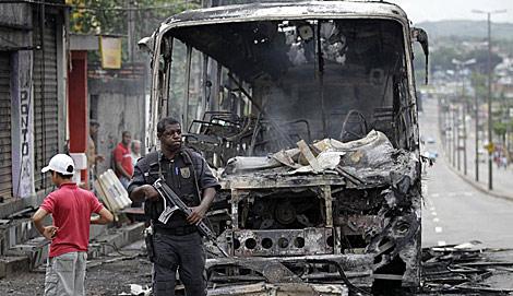 Un policía junto a un autobús incendiado en Santa Cruz, Río de Janeiro.   AP