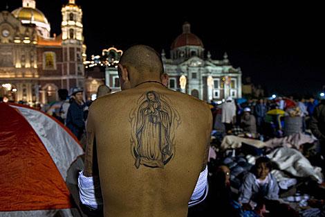 Un peregrino muestra su tatuaje de la Virgen de Guadalupe. | AFP