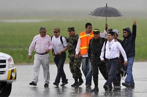 Los liberados Guillermo Solórzano (2d) y Salín Sanmiguel (2i) llegan al aeropuerto de Palmira. | AFP