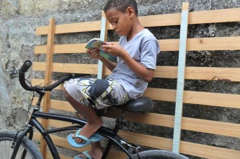 Un niño de la favela leyendo un cuento.| Ediciones Ambulantes