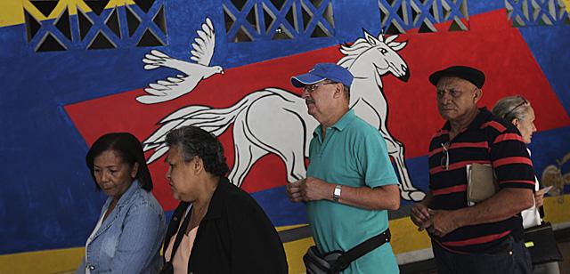Venezolanos hacen cola para votar en Caracas. | Reuters MÁS FOTOS