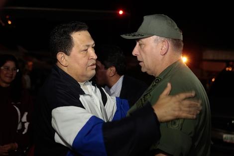 Hugo Chávez saluda a uno de sus ministros en el aeropuerto de Caracas. | Afp