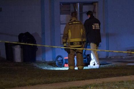 Dos técnicos realizan exámenes al suelo alrededor de la casa.   Tampa Bay Times