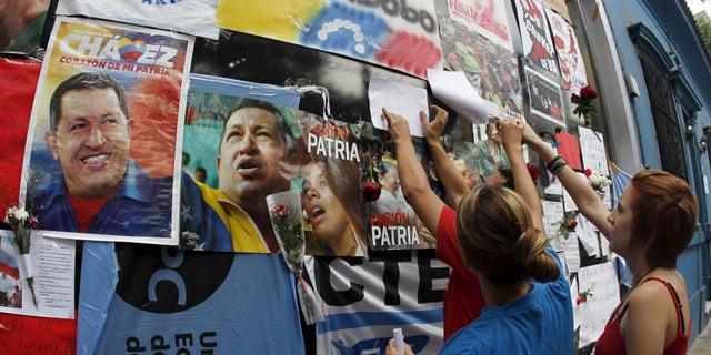 Varias personas dejan mensajes de condolencia en una pared llena de imágenes de Chávez. | Reuters