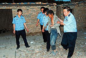 Tres policías ayudan a salir a uno de los trabajadores esclavizados en una fábrica. (Foto: AFP)