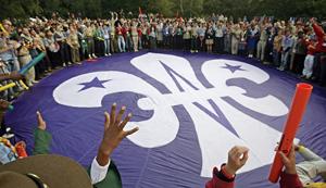 Varios scouts alrededor del emblema de la flor de lis del movimiento en la ceremonia de Brownsea. (Foto: AFP )