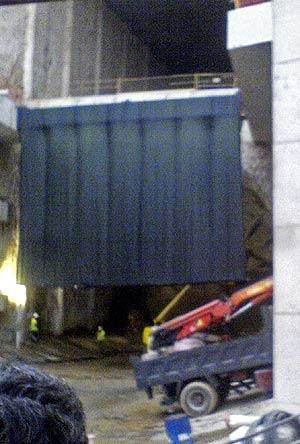Los operarios colocan una tela tras la que se ve la tuneladora. (Foto: EL MUNDO)