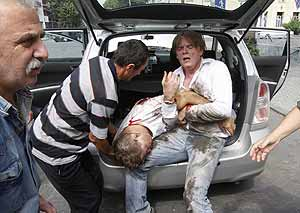 Un periodista holandés saca a un compañero muerto del maletero de un coche. (Foto: REUTERS)
