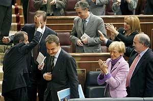 El diputado Francisco Fernández Marugán recibe la felicitación de su grupo, ayer, al término del Pleno presupuestario, junto a Zapatero, De la Vega, Alonso y Solbes. (Foto: EFE)