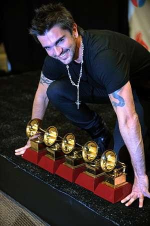Juanes muestra a la cámara los galardones obtenidos. (Foto: AFP)