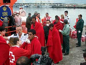 Voluntarios de Cruz Roja y la Guardia Civil atienden a varios inmigrantes. (Foto: Paco Ayala)