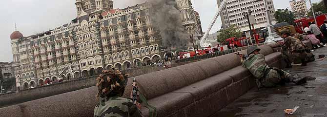 Los policías vigilan de cerca el hotel Taj Mahal (India), mientras los bomberos sofocan las llamas. (Foto: EFE)