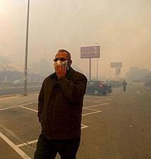 Un vecino de La Nuncia (Alicante), se protege de humo que ha provocado el incendio en la zona. | EFE