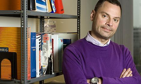 Ioannis Ikonomuo posa delante de algunos diccionarios.
