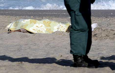 Un agente de la Guardia Civil, junto al cadáver del inmigrante. | Efe