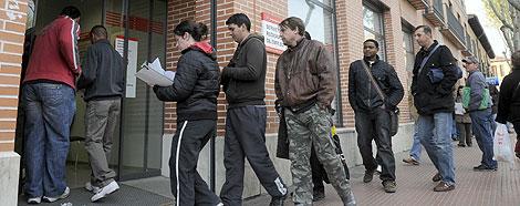 Varias personas, entre ellas algunos inmigrantes, hacen cola en una oficina de empleo. | Efe