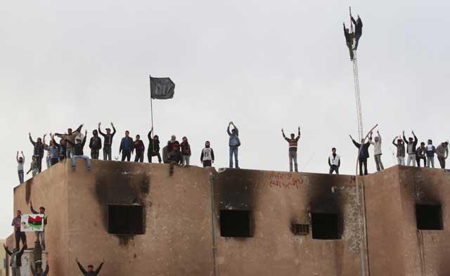 Detractores del régimen de Gadafi, en lo alto del Ayuntamiento, tras tomar Tobruk. | Reuters