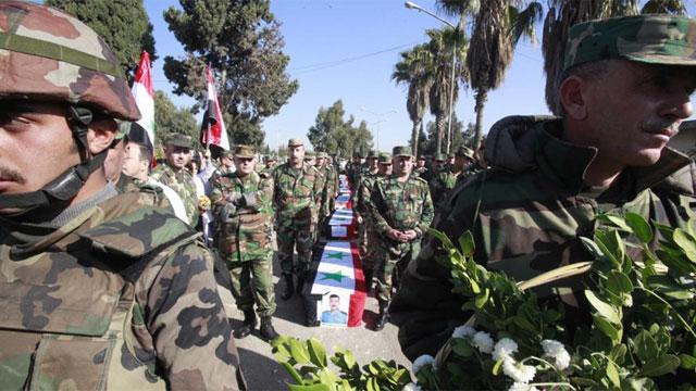 Soldados sirios asisten al funeral de compañeros fallecidos en la provincia de Homs (Siria). | Efe