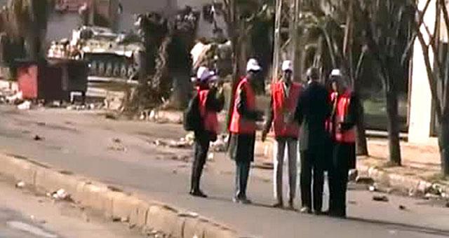 Los observadores de la Liga Árabe, en Homs; al fondo, un tanque. | YouTube