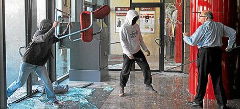 Un empleado 'defiende' su sucursal en las protestas estudiantiles en Barcelona. | Reuters