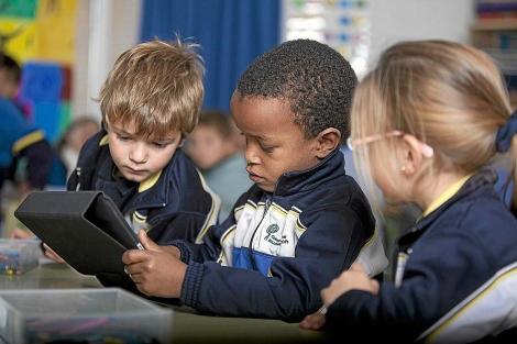 Tres niños aprenden con un iPad en el colegio Ausiàs March (Valencia).| César Conti