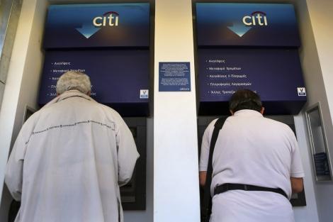 Dos hombres sacan dinero de un cajero en Atenas. | Reuters