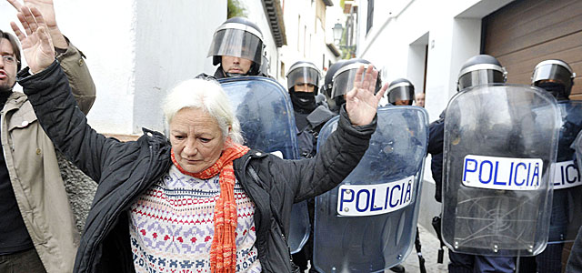 Una mujer desahuciada en Granada ante la Policía. | Jesus Garcia Hinchado