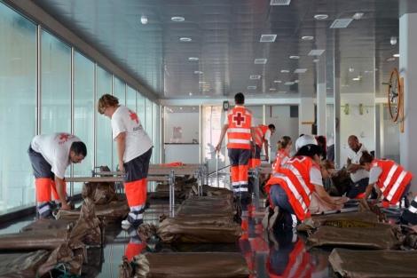 Voluntarios de Cruz Roja preparan camas para desalojados por el terremoto de Lorca. | P. J. Valeros