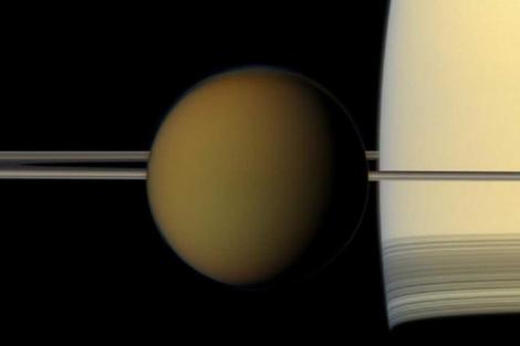 Titán (i) durante su órbita alrededor de Saturno. | NASA