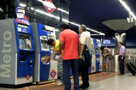 Usuarios de Metro ante unas másquinas expendedoras de billetes.| E. M.