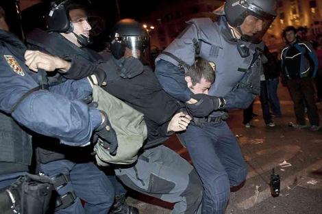 Los antidisturbios deteniendo a un manifestante en la Plaza de Neptuno. | Efe