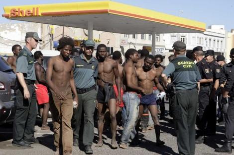 Algunos de los inmigrantes custodiados por la Guardia Civil. | Francisco Guerrero / Efe