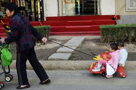 Una mujer arrastra un carrito con dos niños en Pekín. | Afp