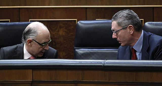 El ministro de Hacienda, Cristóbal Montoro, habla con el de Justicia, Alberto Ruiz-Gallardón, en el Congreso. | Efe