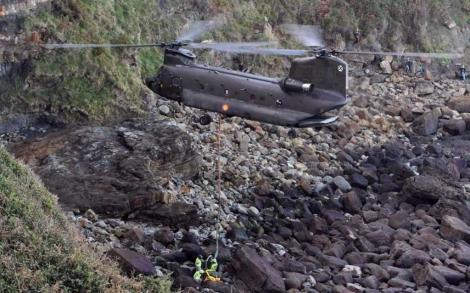 El helicóptero recogiendo la roca con el fósil. | Efe