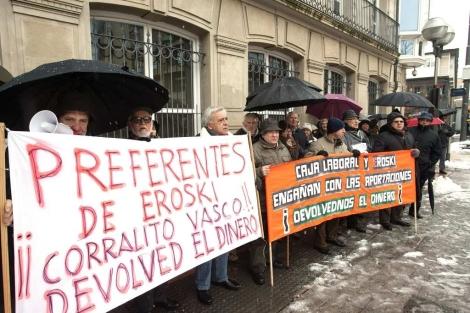 Decenas de afectados por las preferentes del grupo Mondragón frente al Parlamento. | Efe