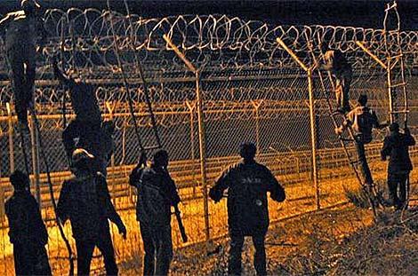 Inmigrantes saltando la valla de Melilla en 2012. | El Mundo