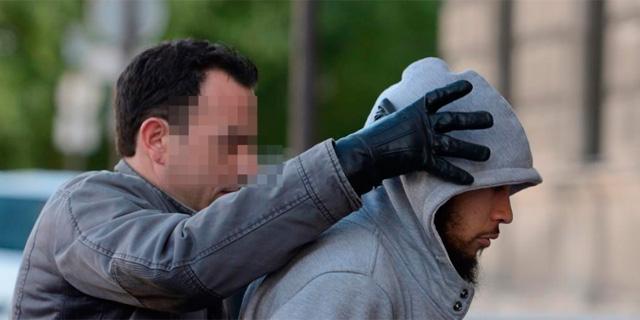El detenido, custodiado por un policía. | Afp