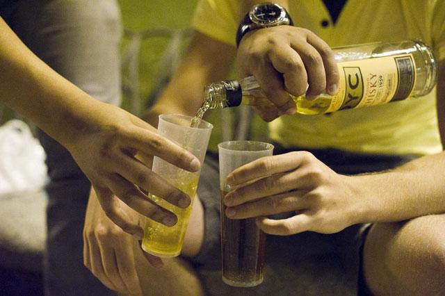 Varios jóvenes se sirven whisky en un botellón en Madrid. | EL MUNDO