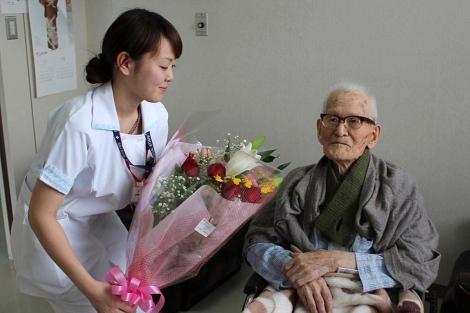 Una enfermera entrega un ramo de flores al japonés Jiroemon Kimura. | Afp