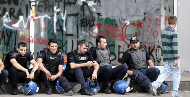 Policías turcos antidisturbios delante de una sucursal bancaria dañada en la plaza Taksim. | Efe