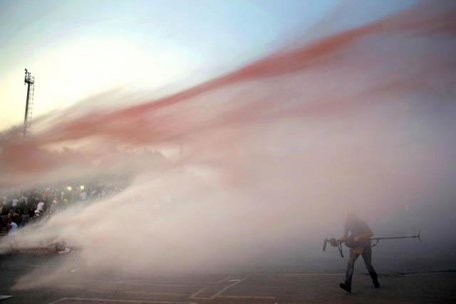 Una nube de gas lacrimógeno envuelve a un manifestante. | Reuters. VEA MÁS IMÁGENES