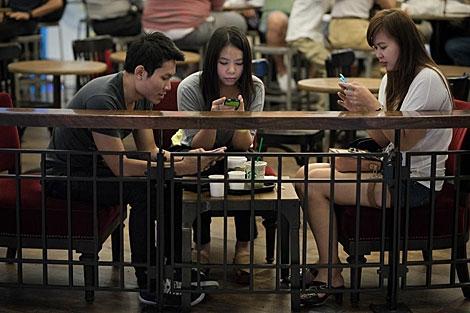 Usuarios de móviles en Bangkok. | Afp