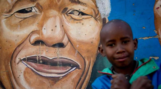 Un niño frente a una pintura con la imagen de Madiba. | Afp